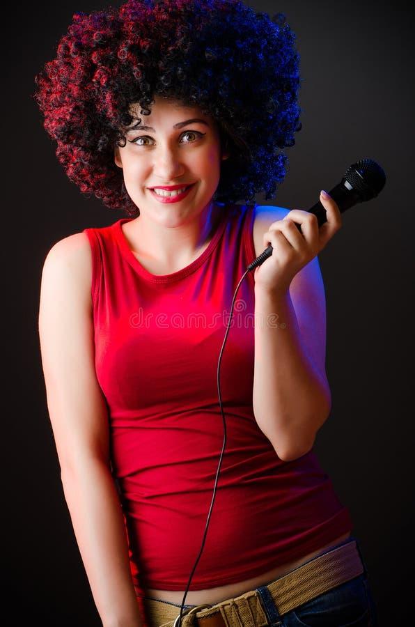 有非洲的发型的妇女唱歌在卡拉OK演唱的 库存图片