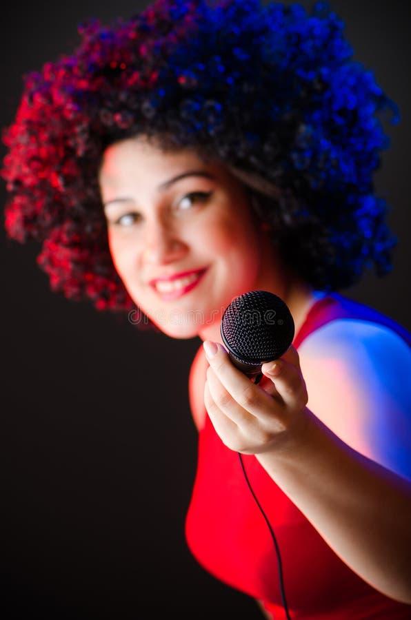 有非洲的发型的妇女唱歌在卡拉OK演唱的 免版税库存图片