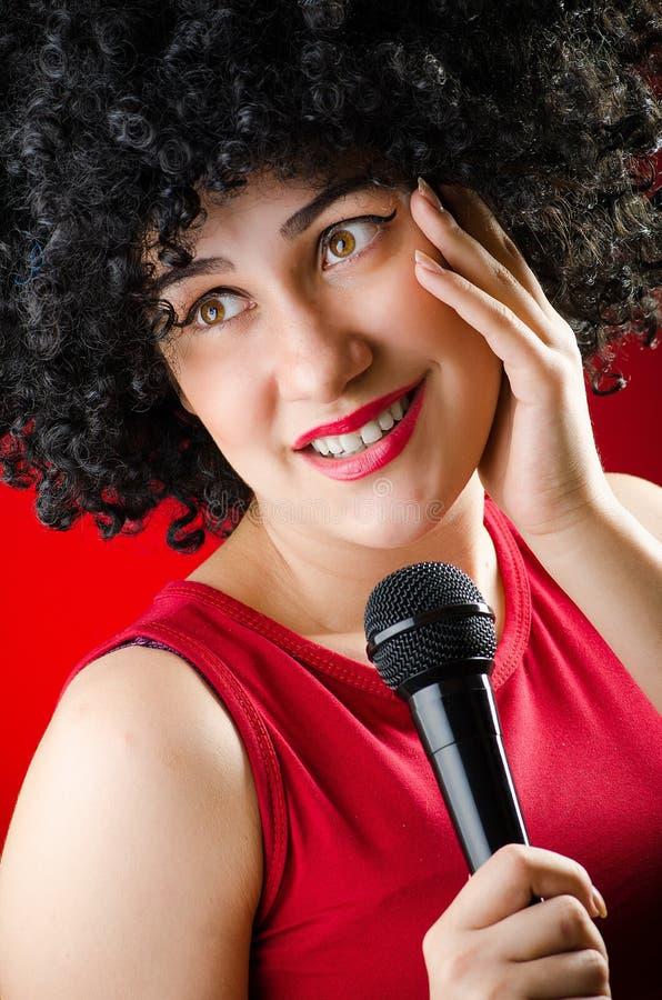 有非洲的发型的妇女唱歌在卡拉OK演唱的 图库摄影