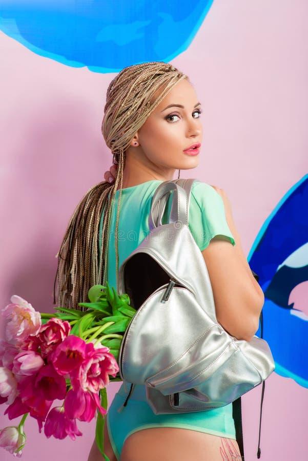 有非洲辫子的美丽的可爱的白肤金发的少妇与在桃红色背景的郁金香 图库摄影