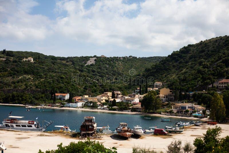 有靠码头的小船的传统渔镇,有lakeviews的山村,渔夫湖公共海岸线的,绿色H 免版税库存图片