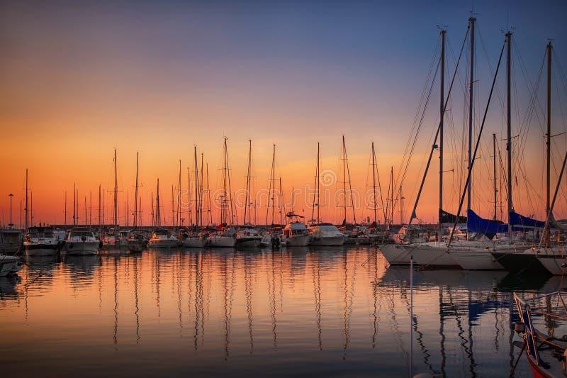 有靠码头的游艇的小游艇船坞在日落 库存图片