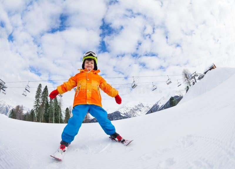 有面具和盔甲滑雪的男孩在滑雪胜地 免版税库存图片