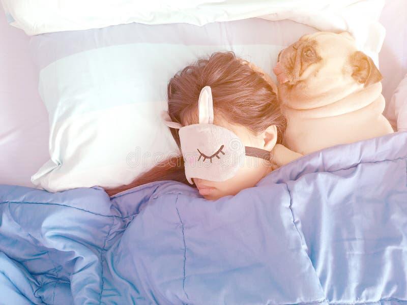 有面具和逗人喜爱的小狗哈巴狗狗的甜亚裔妇女是睡觉休息在床上 免版税库存图片