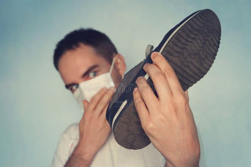 有面具的人拿着肮脏的腐败的鞋子-令人不快的气味概念 肮脏的有臭味的运动鞋 免版税库存照片