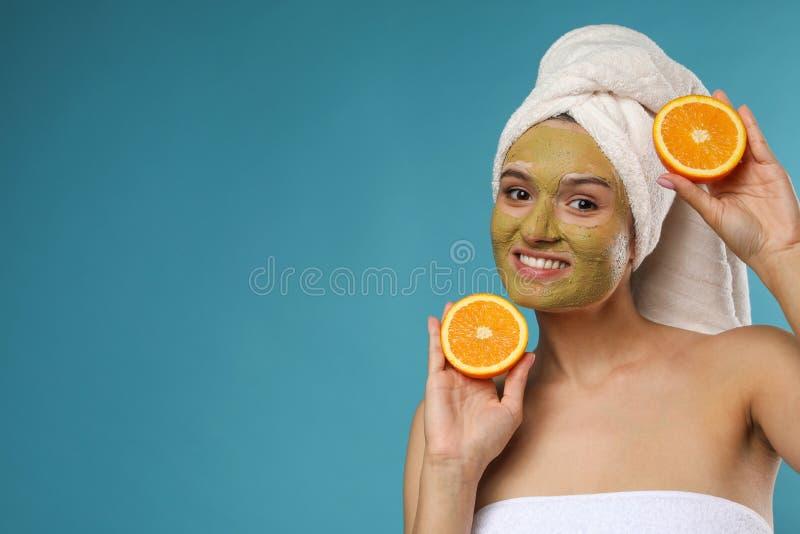 有面具的美女在反对颜色背景的面孔和裁减桔子 免版税库存照片