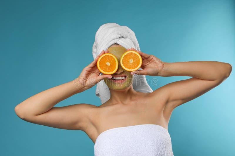有面具的美女在面孔和裁减桔子 免版税库存照片