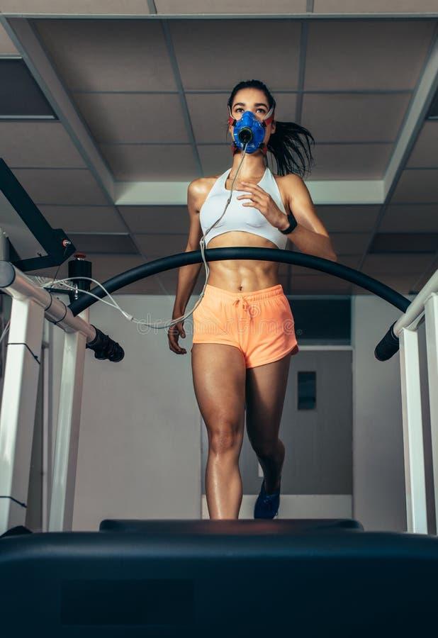 有面具的赛跑者在踏车在体育科学实验室 免版税库存图片