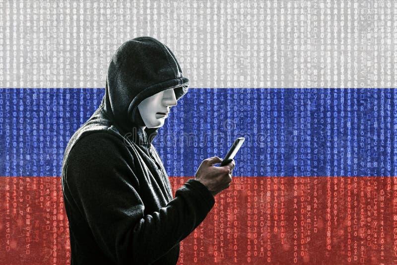 有面具藏品智能手机的俄国戴头巾黑客 库存照片