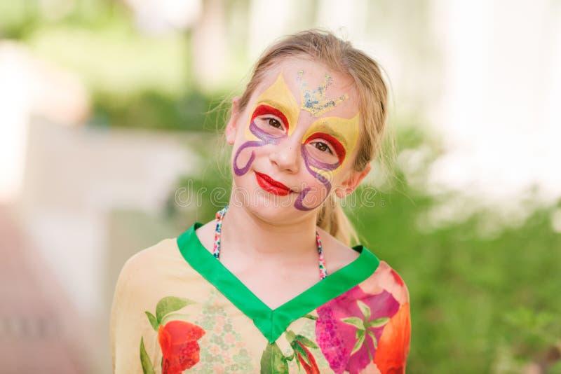 有面孔艺术油漆的愉快的小女孩在公园 库存图片