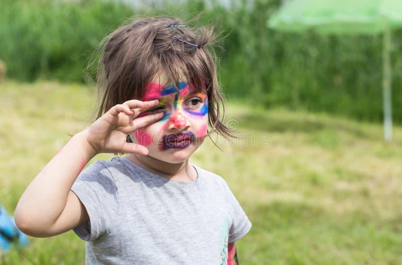 有面孔艺术绘画的微笑的女孩象老虎,做面孔绘画,万圣节聚会,有滑稽的面孔绘画的孩子的小男孩 库存图片