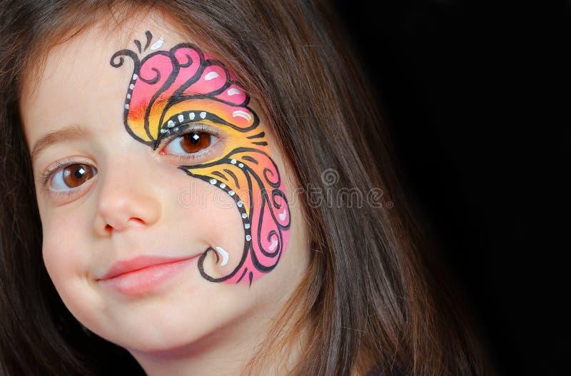 有面孔绘画的俏丽的女孩 免版税图库摄影