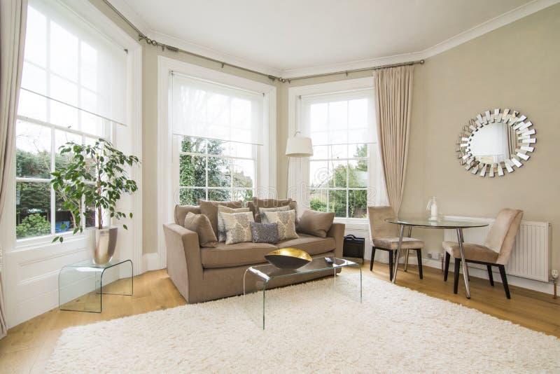有面对可爱的庭院的大凸出的三面窗的经典客厅 图库摄影