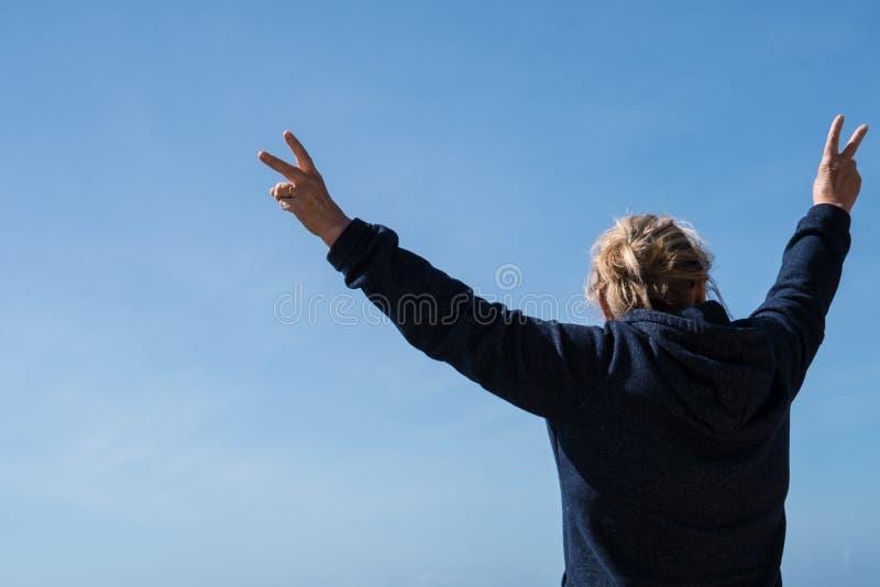 有面对照相机的后面的资深妇女握她的做和平标志的胳膊反对天空蔚蓝 自由的,退休概念 免版税库存图片