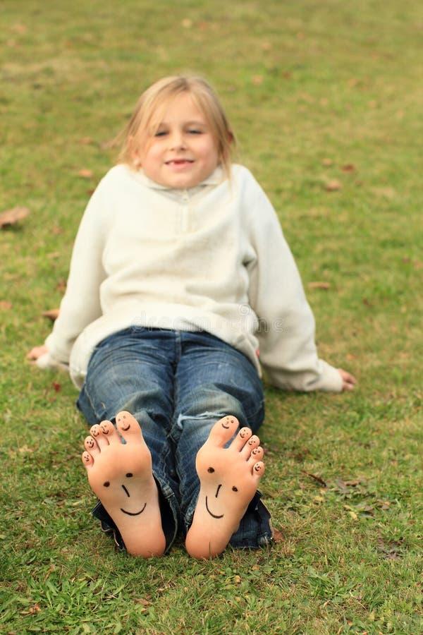 有面带笑容的女孩在脚趾和鞋底 免版税库存照片