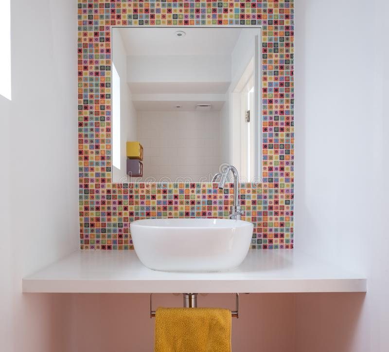 有面盆的,五颜六色的玻璃锦砖当代卫生间,绘了MDF架子和镜子插页入瓦片 库存照片