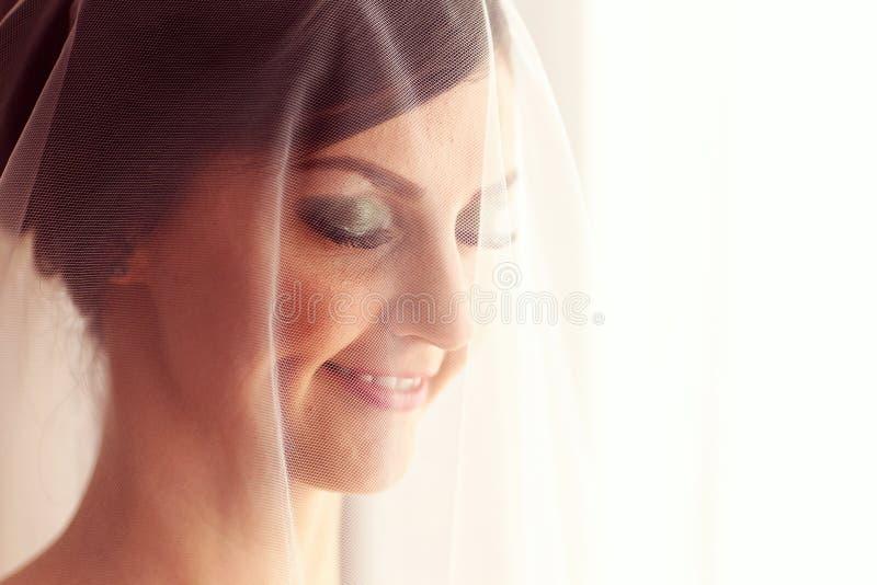 有面纱的美丽的新娘在她的屋子里 免版税库存照片