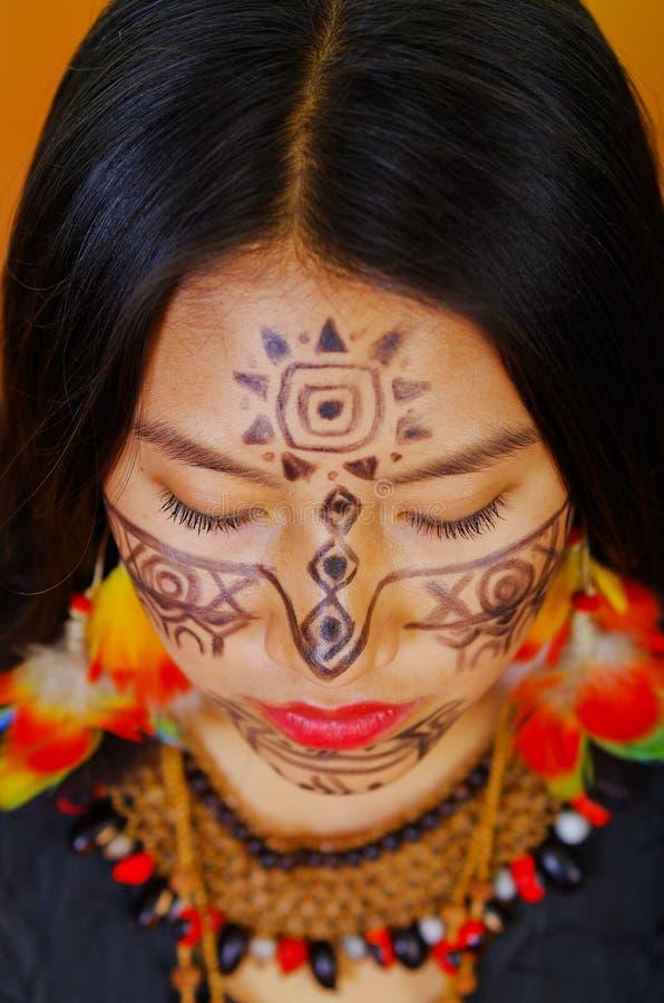 有面部油漆和黑礼服的特写美丽的似亚马逊异乎寻常的妇女,严重摆在为照相机,森林 免版税库存照片