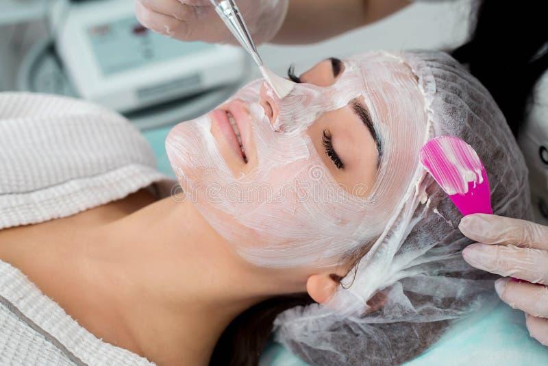 有面部面具的美丽的妇女在美容院 免版税库存照片