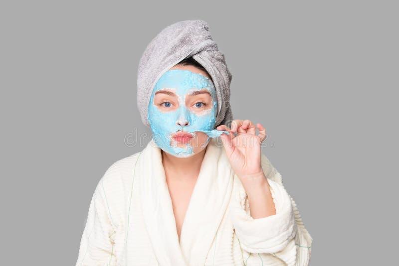 有面部黏土面具的妇女在温泉沙龙或在家,skincare题材 女孩去除藻酸盐化妆面具 面膜,温泉 免版税图库摄影