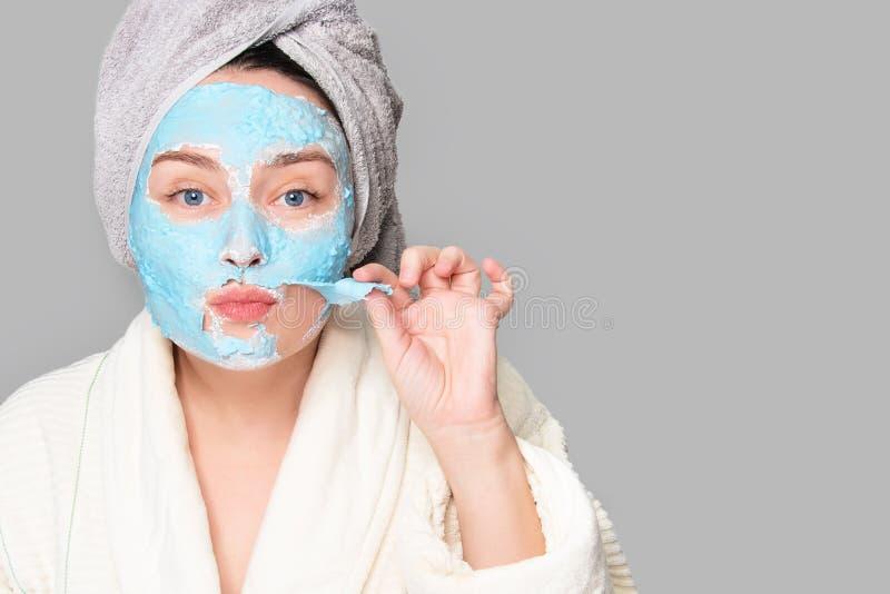 有面部黏土面具的妇女在温泉沙龙或在家,skincare题材 女孩去除藻酸盐化妆面具 面膜,温泉 库存图片