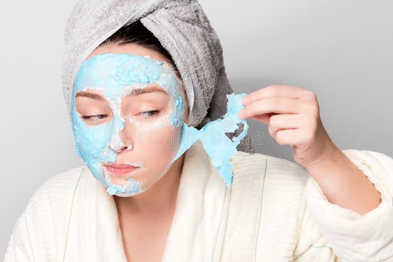 有面部黏土面具的妇女在温泉沙龙或在家,skincare题材 女孩去除藻酸盐化妆面具 面膜,温泉 免版税库存图片