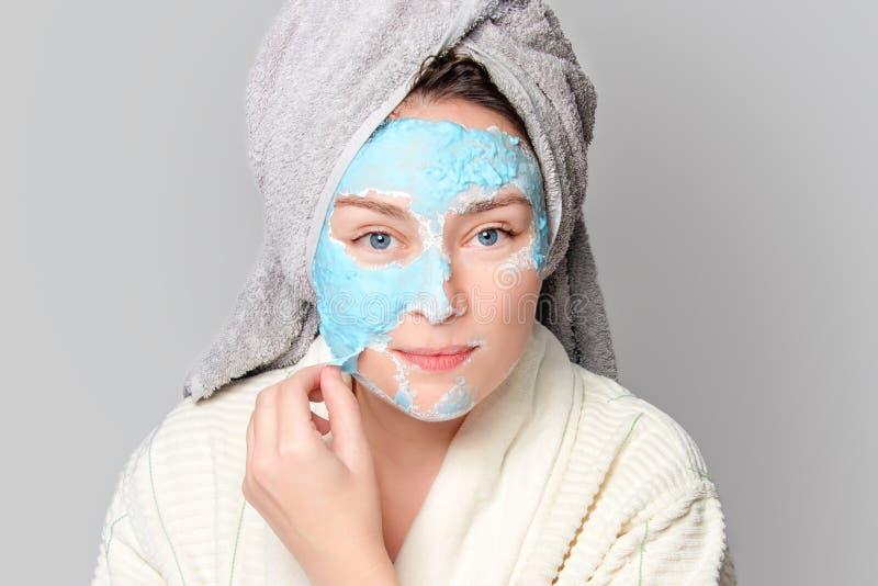 有面部黏土面具的妇女在温泉沙龙或在家,skincare题材 女孩去除藻酸盐化妆面具 面膜,温泉 库存照片