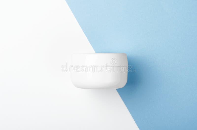 有面霜的白色瓶子在白色和蓝色背景 化妆品 o 免版税库存照片