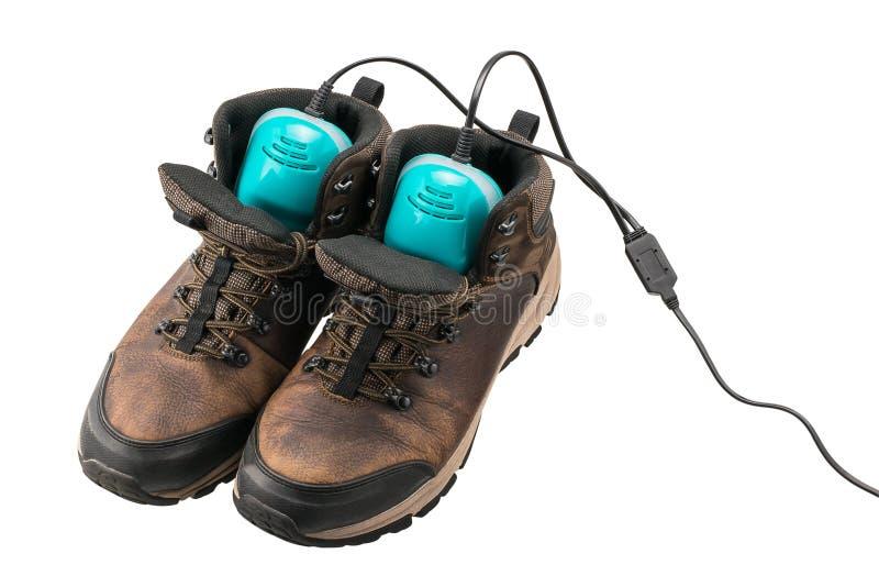 有鞋子烘干机的人` s皮靴 库存图片