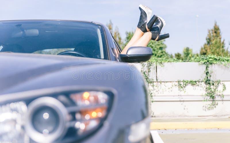 有鞋子的年轻凉快的女孩在享受看法的汽车窗口外面 免版税库存照片