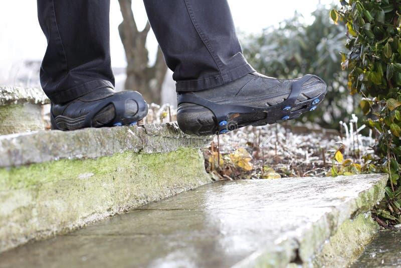 有鞋子雪钉的人在冰冷的台阶的冬天 库存图片