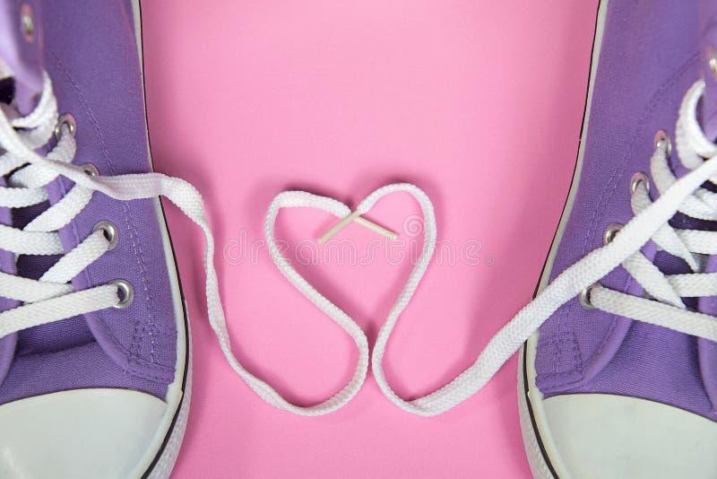 有鞋带心脏的紫色运动鞋 免版税库存照片