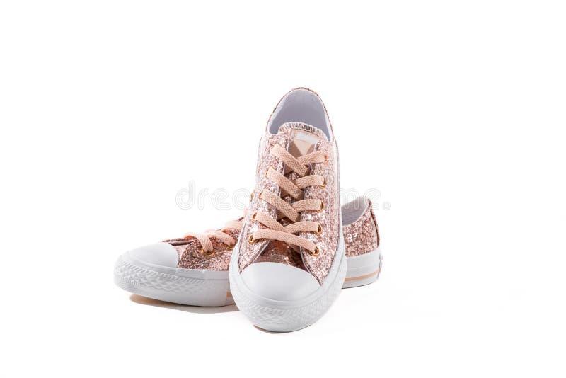 有鞋带的桃红色闪闪发光闪烁女孩运动鞋 免版税库存照片