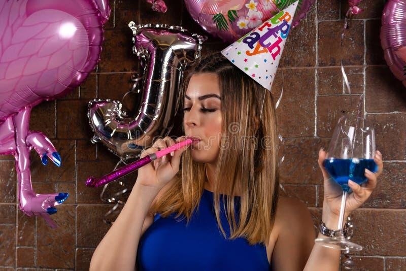 有音乐爆胎和鸡尾酒蓝色盐水湖的愉快的在头的美女在手中和盖帽庆祝她的生日 库存图片
