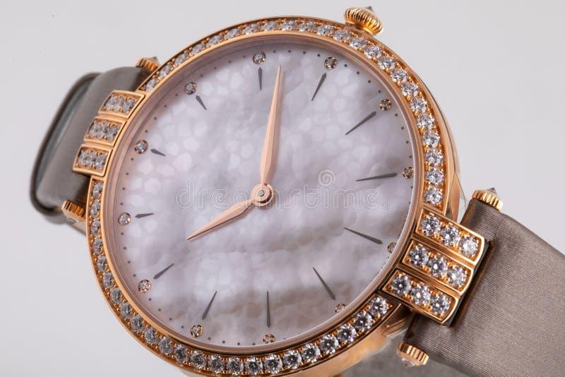 有顺时针方向一个灰色拨号盘的女性金表,金黄,构筑石头,与一条棕色布料皮带 免版税库存图片