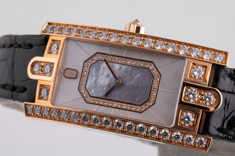 有顺时针方向一个灰色拨号盘的女性金黄手表,黑,构筑石头,与黑皮带 库存照片