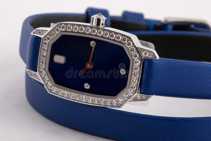有顺时针方向一个蓝色拨号盘的女性银色手表,棕色,构筑石头,与一条蓝色布料皮带 库存照片