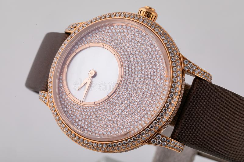 有顺时针方向拨号盘的女性金手表从石头,金黄,在白色背景的棕色布料皮带 库存照片