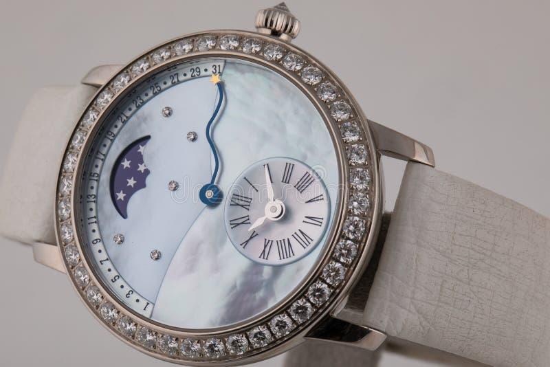 有顺时针方向白色拨号盘的女性银色手表,银色与在白色背景隔绝的白革皮带 免版税库存图片