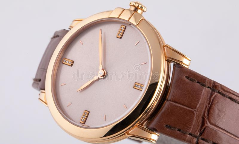 有顺时针方向白色拨号盘的金黄手表,金黄,在白色背景隔绝的棕色皮带 库存照片
