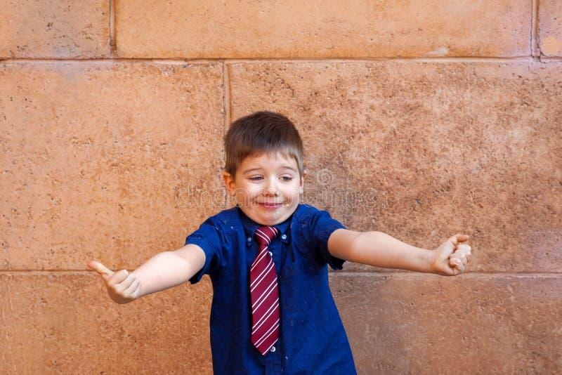 有领带的穿着体面的男孩给婚宴喜饼的赞许 库存照片