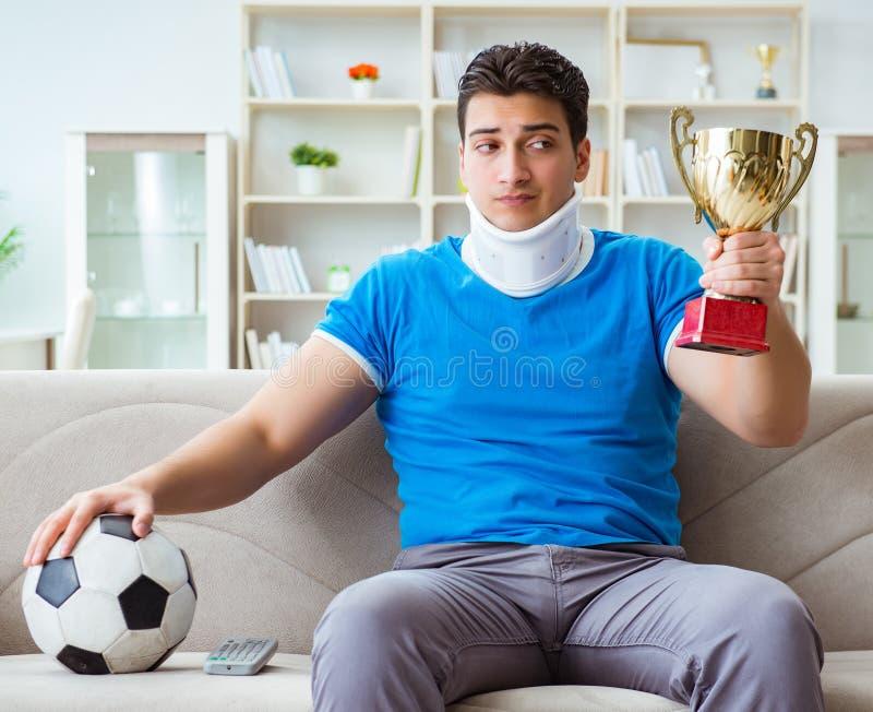 有颈部受伤观看的橄榄球足球的人在家 免版税库存照片