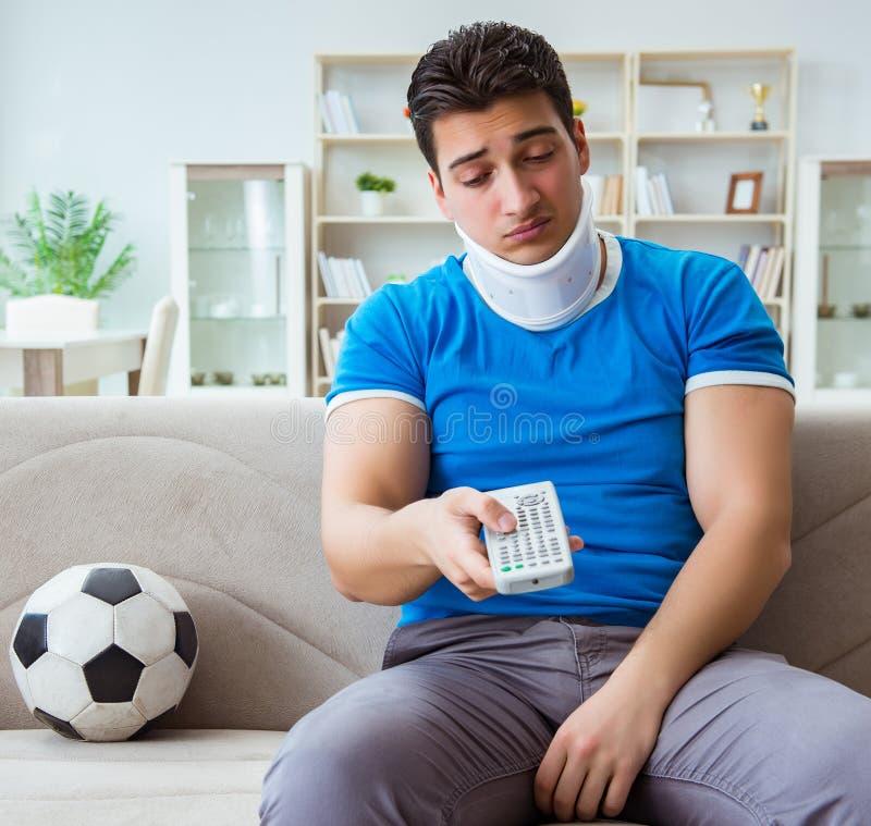 有颈部受伤观看的橄榄球足球的人在家 免版税库存图片