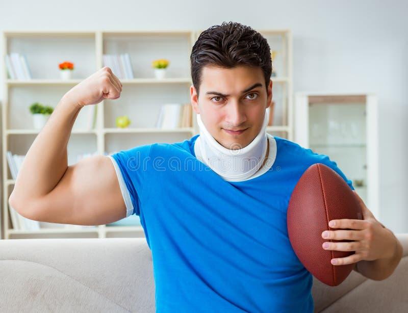 有颈部受伤观看的美式足球的人在家 免版税图库摄影