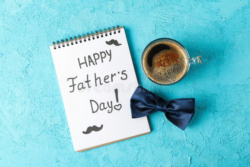 有题字愉快的父亲节、蓝色蝶形领结和咖啡的笔记本在颜色背景,文本的空间的 库存图片