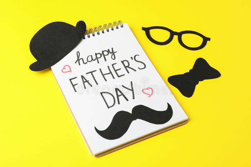 有题字愉快的父亲节、装饰蝶形领结、玻璃、髭和帽子的笔记本在颜色背景 免版税库存图片