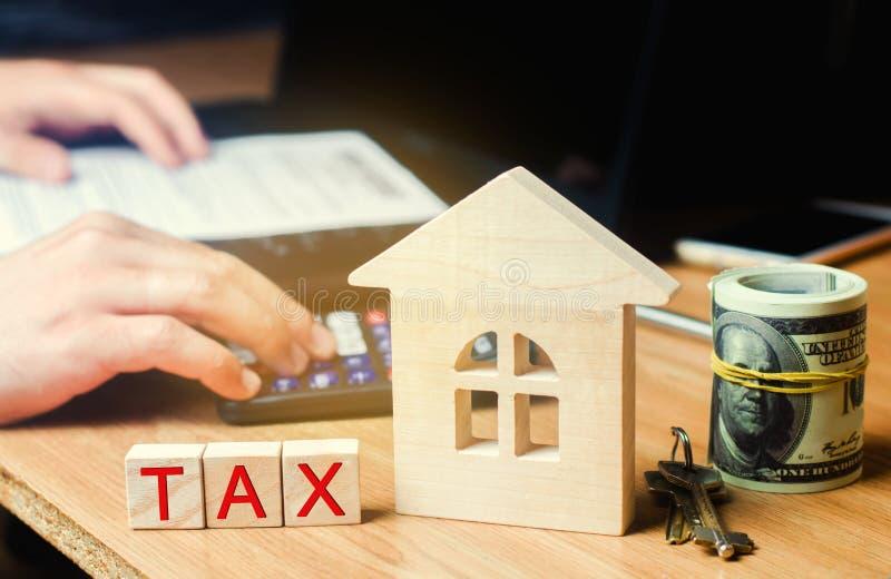 有题字的'税'木房子 在房地产,付款的税 惩罚,欠款 纳税人记数器物产的 法律 免版税图库摄影