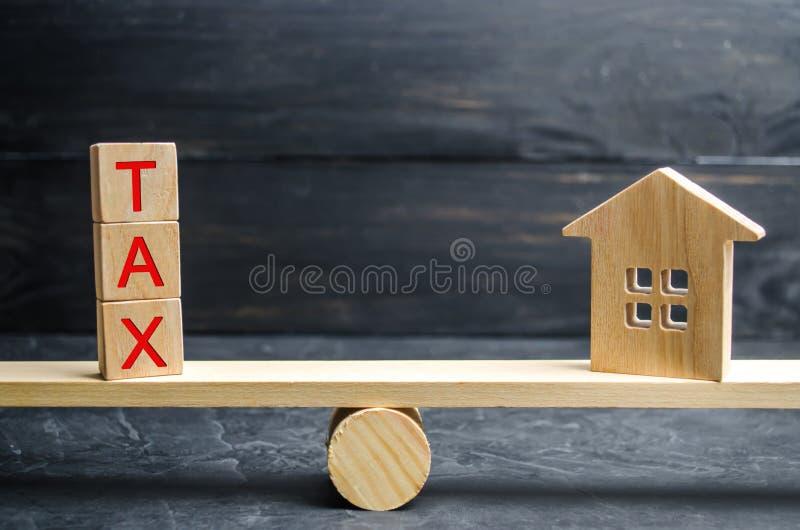 有题字`税`的木房子在等级 在房地产,付款的税 惩罚,欠款 纳税人记数器为 库存照片