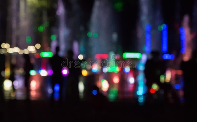 有颜色照明的城市喷泉在焦点外面的晚上 免版税库存图片