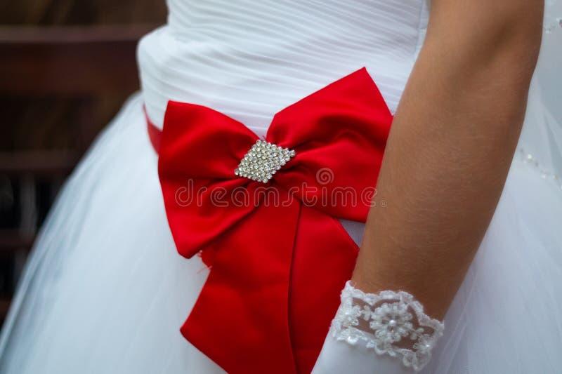 有颜色红色弓的新娘的白色礼服在特写镜头视图 蓝色详细资料花袜带系带婚礼 免版税库存照片
